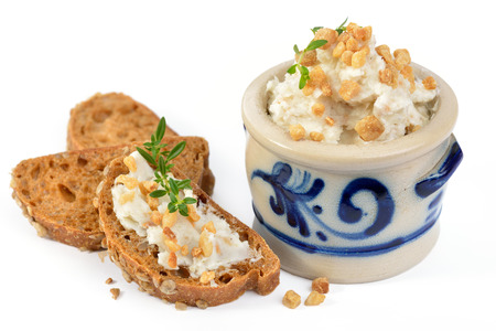 German spicy crackling lard in a rustic stoneware pot and as a spread on rye bread with thyme Standard-Bild