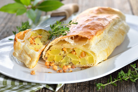 Hearty Austrian cuisine: Potato strudel with eggs and greaves, served on a wooden table