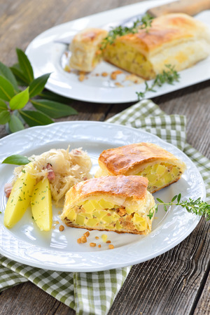 Hearty Austrian cuisine: Potato strudel with greaves, served with bacon Sauerkraut Stock Photo