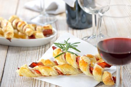 Pečené vydatné listového těsta tyčinky se šunkou a bylinkami se sklenkou červeného vína