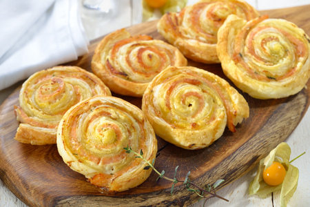 Baked hearty puff pastry rolls with smoked slamon, cream cheese and fesh herbs Stock Photo