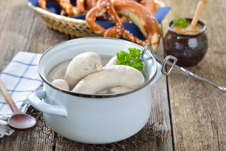 breadbasket: Hot Bavarian white sausages in to enamel cooking pot served on a wooden table with fresh pretzels and sweet mustard
