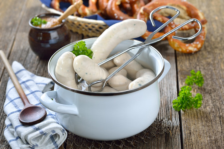 Hot Bavarian white sausages in to enamel cooking pot served on a wooden table with fresh pretzels and sweet mustard