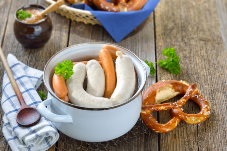 Hot Bavarian white sausages and wieners on in enamel cooking pot served on a wooden table with fresh pretzels and sweet mustard Reklamní fotografie