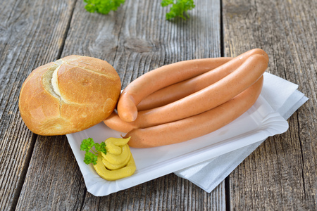 German street food: Four wieners with a fresh roll and spicy mustard on a paper plate Reklamní fotografie