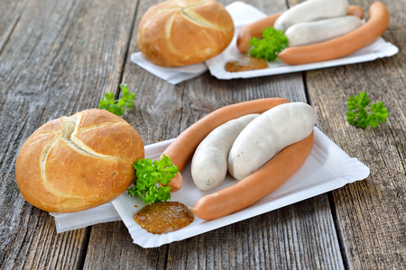 veal sausage: German street food: Bavarian white sausages and wieners with a fresh roll and sweet mustard on a paper plate