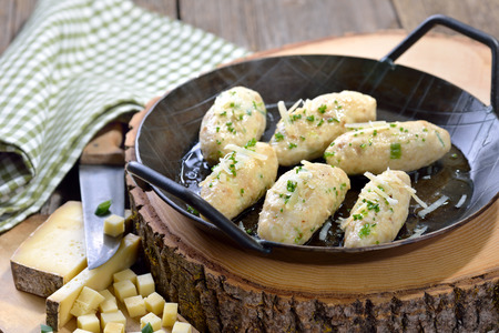 Traditional South Tyrolean cheese dumplings (so-called Kasnocken) made of white bread and hearty mountain cheese, served with melted butter, grated parmesan and chives