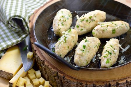 """Tradiční tyrolské sýrové knedlíky (tzv. """"Kasnocken"""") z bílého chleba a srdečného sýrového sýra podávané s roztaveným máslem, strouhaným parmazánem a pažitkou"""