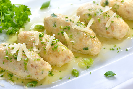 Traditional South Tyrolean cheese dumplings (so-called Kasnocken) made of white bread and hearty mountain cheese, served with melted butter, grated parmesan and chives on a white platter Stock Photo