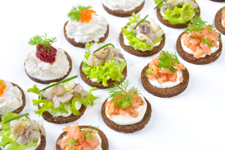 godfather: Tasty fish finger food with smoked salmon tartar, trout mousse with caviar and herring salad on pumpernickel bread Stock Photo