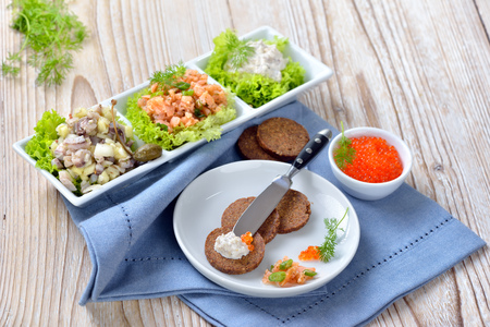 Mixed cold fish snack with smoked salmon tartar, trout mousse, caviar and salted herring salad, served as appetizer at withround pumpernickel bread slices
