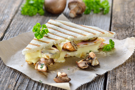 Pressed and toasted double panini with ham, cheese and mushrooms served on sandwich paper on a wooden table Reklamní fotografie