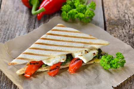 Vegetarian toast: Panini with grilled red bell peppers and feta cheese on pesto sauce, served on sandwich paper on a wooden table