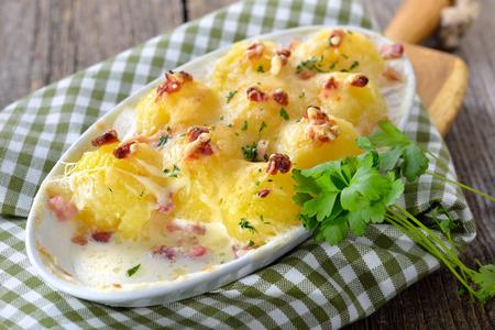 Hezké bramborové knedlíky pečené se sýrem a slaninou, čerstvě podávané z trouby