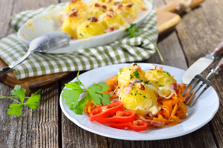 Hearty potato dumpling gratin with cheese and bacon served on paprika cabbage Stock Photo