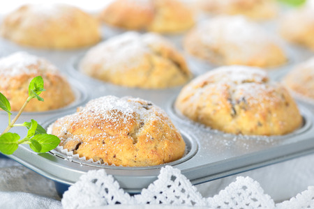 Freshly baked chocolate banana muffins in the baking pan dusted with icing sugar