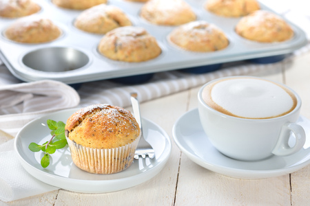 Freshly baked chocolate banana muffins with icing sugar served with a cup of cappuccino