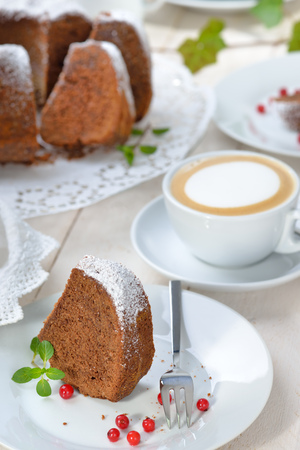 Freshly baked ring-shaped cake with chocolate, so called Gugelhupf in Austria and Germany, served with a cup of cappuccino
