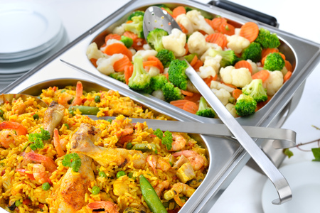 Hot buffet with Spanish paella and mixed buttered vegetables served in a chafing dish