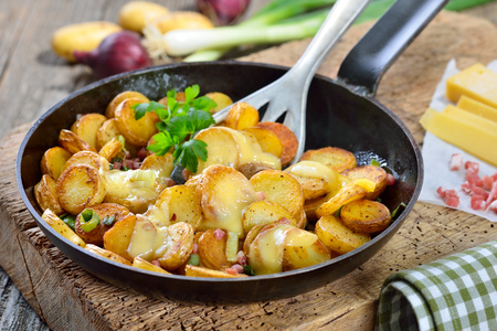 Fried potatoes unpeeled baby with melted mountain cheese and bacon cubes