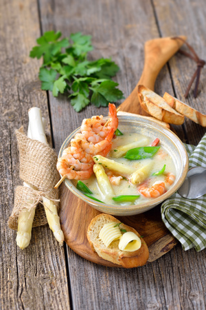 Cream of asparagus soup with fried prawns and snow peas, served with toasted baguette with butter rolls