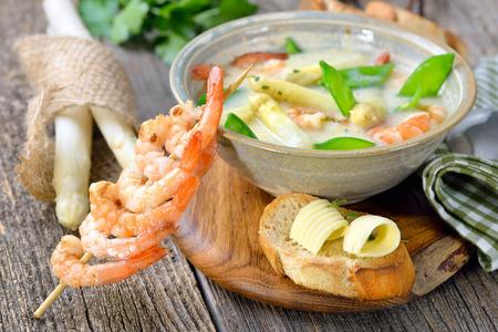 Krém chřestové polévky se smaženými krevety a sněhem, podávaný s opékanou bagetou s máslovými rolky Reklamní fotografie
