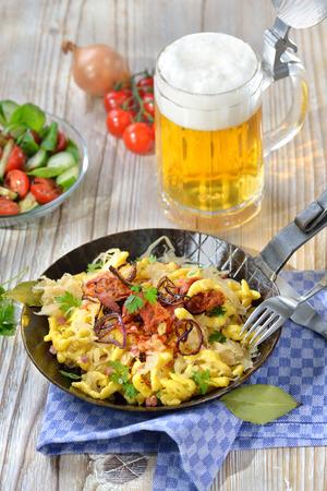 Švábské smažené brambory na dřevěném stole s pivem a vedlejším salátem