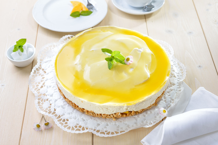 Fresh cheesecake with mango fruit and glace, the flan case made of cookie crumbs