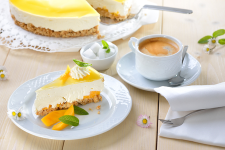 Fresh cheesecake with mango fruit and glaze, served with a cup of coffee Reklamní fotografie