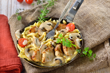 Fried medallions of pork fillet with swabian spaetzle (so called Schwabenpfandl or Schwabentopf) and mushroom cream sauce served in an iron frying pan on a rustic table with an old jute sack