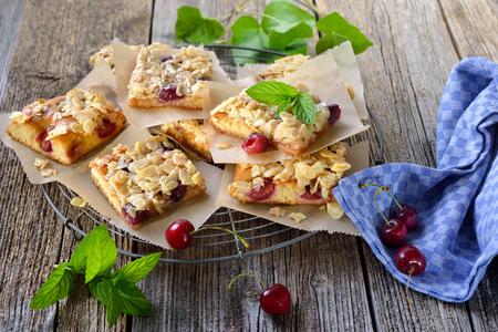 Čerstvý rajský džusový dort s třešněmi a křupavým mandlovým karamelem sloužil na ošumělém chladicím stojanu Reklamní fotografie