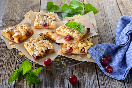 Fresh Austrian yeast cake with cherries and crunchy almond caramel served on a shabby cooling rack