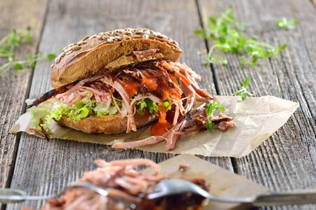Broušený vepřový sendvič na dřevěném stole