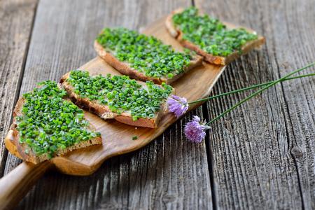 Pivní zahrádka: plátky čerstvého chleba s máslem a nasekané pažitky na dřevěné desce
