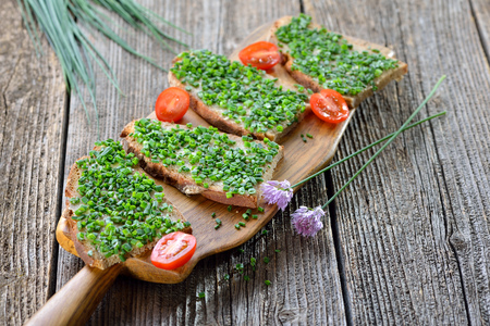 Beer garden food: slices of fresh farmhouse bread with butter and chopped chives on a wooden board Reklamní fotografie - 81996351