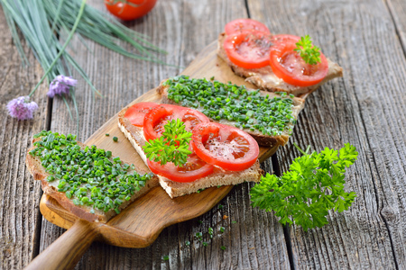 Vegetarian snack: Slices of buttered farmhouse bread with fresh chives and tomatoes on a wooden board Banque d'images