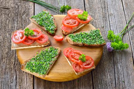 Vegetariánské občerstvení: plátky máslového chleba s čerstvou pažitkou a rajčaty na dřevěné desce Reklamní fotografie