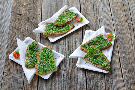 Street food: slices of fresh farmhouse bread with butter and chopped chives on white paper plates