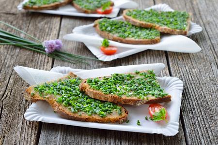 Uliční jídlo: plátky čerstvého chleba s máslem a nasekané pažitky na bílých papírových deskách