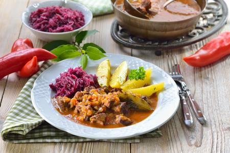 Hot maďarský guláš podávaný s máslovými petrželovými bramborami a červeným zelím