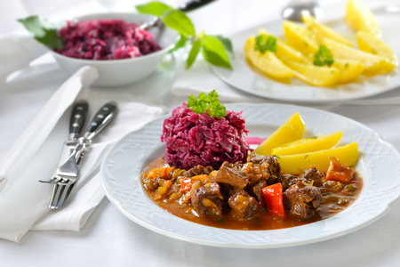 Hot Hungarian goulash served with buttered parsley potatoes and red cabbage