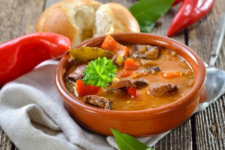 Horká maďarská gulášová polévka se podává v keramické misce s čerstvou rolí