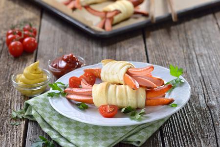 Pečená vídeňská klobása zabalená z mikrovlnné trouby z čerstvého pečiva, často slouží jako dětské jídlo Reklamní fotografie