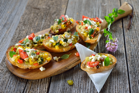 Warm vegetarian canapes: Baked crostini with mixed Greek food with feta cheese served on a wooden cutting board Banque d'images