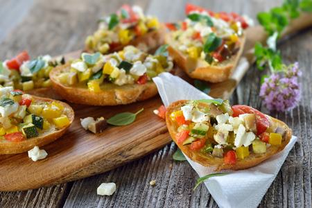 Teplé vegetariánské sýry: Pečené crostini se smíšenými řeckými pokrmy s sýrem feta podávané na dřevěné desce Reklamní fotografie