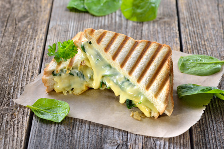 Vegetarian pressed double panini with fresh spinach leaves, onions and cheeses