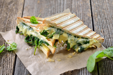 Vegetarian pressed double panini with fresh spinach leaves, onions and cheese