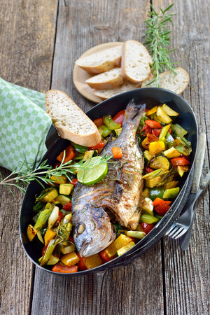 Oven fresh gilthead baked with rosemary on mixed summer vegetables, served with Italian ciabatta bread Banque d'images
