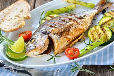 Grilovaný gilthead broskev se smíšenou rozmarýnovou zeleninou podávaný na oválné talíři bílých ryb
