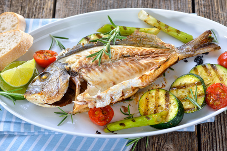 Grilled gilthead seabream with mixed rosemary vegetables served on an oval whitefish plate